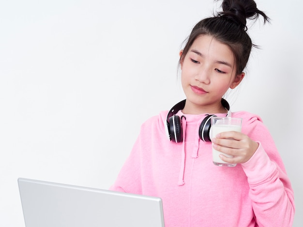 Menina alegre usando laptop sentado na cadeira.
