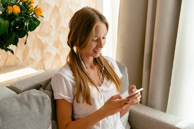 Menina alegre usando smartphone enquanto escuta música em fones de ouvido no sofá em casa
