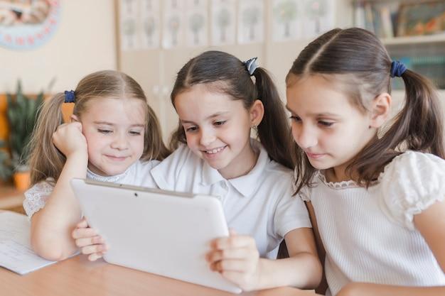 Menina alegre usando tablet em sala de aula
