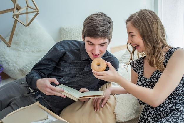 Menina alimenta um cara donut. o menino está lendo livro na cama