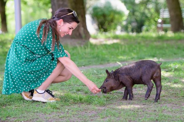 Menina alimenta um porquinho. em um prado verde. o conceito de sustentabilidade, amor à natureza, respeito pela paz e amor pelos animais. ecológico, biológico, vegano, vegetariano