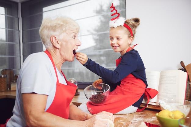 Menina alimentando a avó com frutas secas