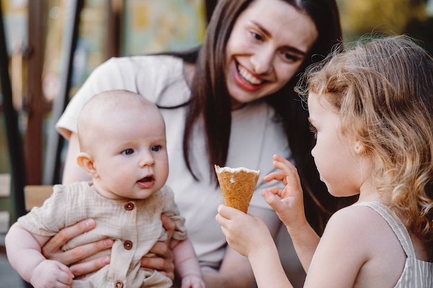 Menina alimentando irmão bebê com casquinha de sorvete