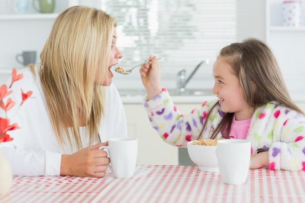 Menina alimentando sua mãe