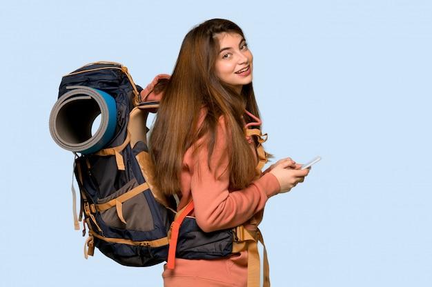 Menina alpinista, enviando uma mensagem com o celular em azul
