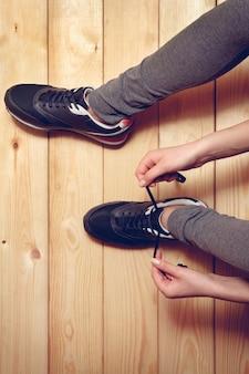 Menina amarrando cadarços sentada no chão de madeira