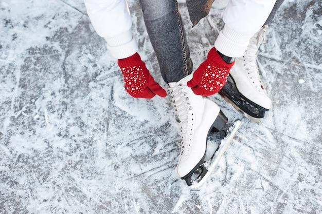 Menina amarrar cadarços em patins de gelo antes de patinar na pista de gelo, mãos em luvas de malha vermelhas.