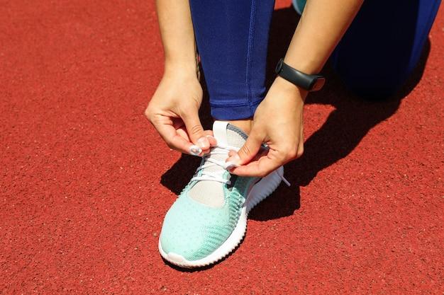 Menina, amarrar cadarços na pista de atletismo vermelha, espaço para texto