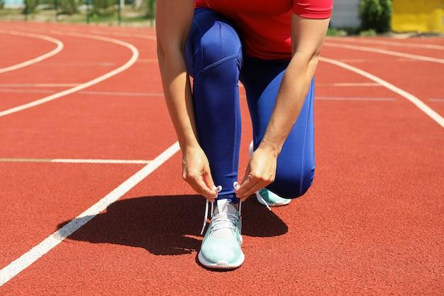 Menina amarrar cadarços na pista de corrida atlética vermelha, copie o espaço