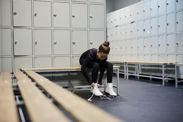 Menina amarrar patins no camarim