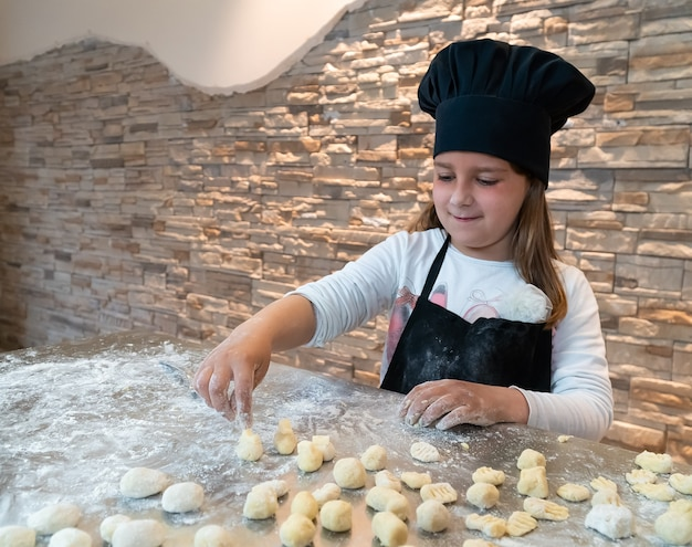 Menina amassando nhoque vestida de chef