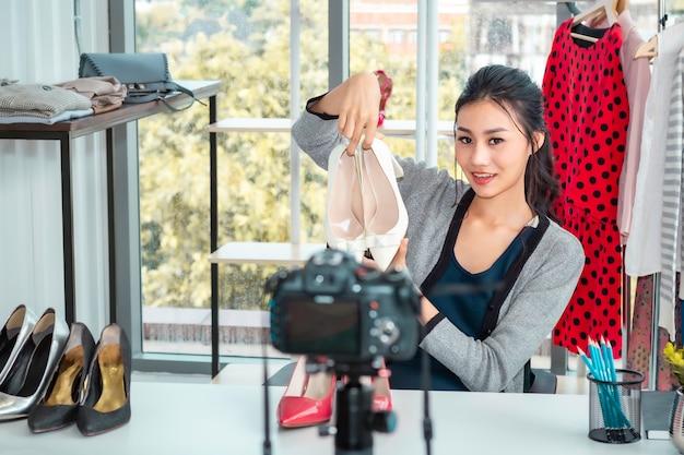 Menina amigável da ásia jovem, blog de vídeo ao vivo e sapatos de vendas em compras de comércio eletrônico on-line