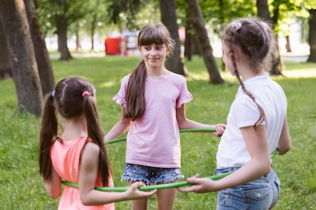 Menina amigos, tocando, com, hula hoop