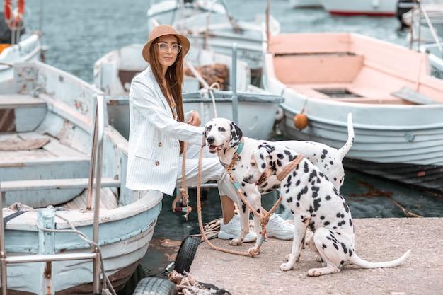 Menina anda com animal de estimação, adulto dálmata à beira-mar com transporte de água