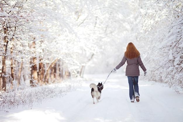 Menina anda com um cachorro no parque no inverno