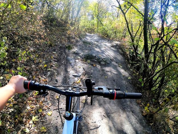 Menina anda de bicicleta pela floresta. menina anda de bicicleta ao longo do caminho na floresta no outono com luz solar. câmera de ação pov profissional. conceito de aventura esporte estilo de vida ativo. vista da perspectiva de primeira pessoa