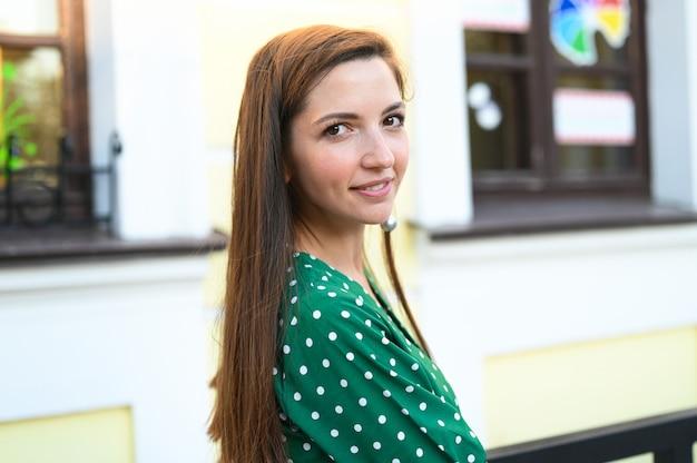 Menina anda pela cidade em um vestido verde de bolinhas