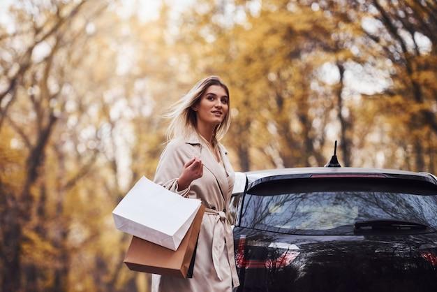 Menina anda perto do carro com sacolas de compras nas mãos. automóvel novo moderno na floresta.