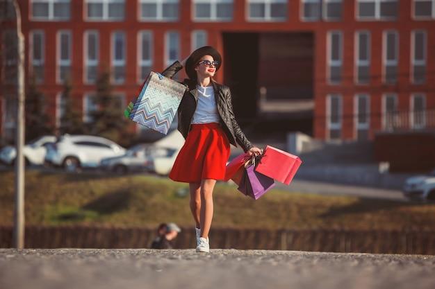 Menina andando com as compras nas ruas da cidade