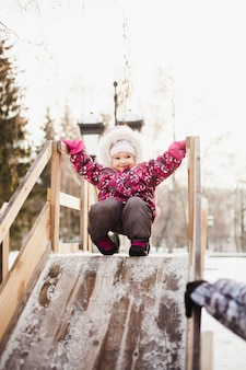 Menina andando com montanha-russa de madeira, inverno e diversão
