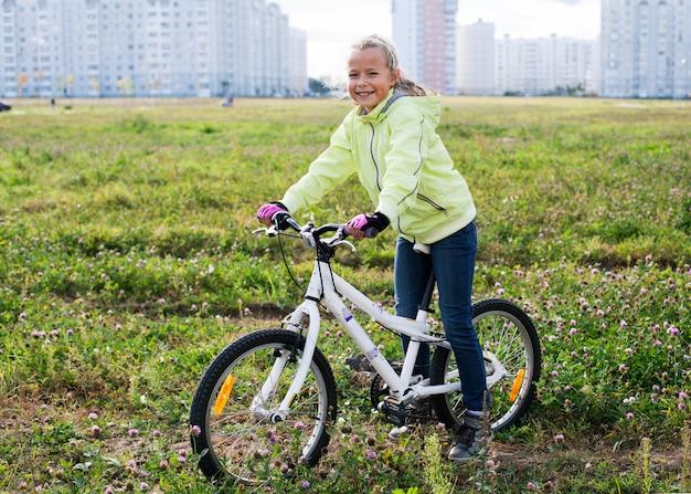 Menina andando de bicicleta em um campo verde