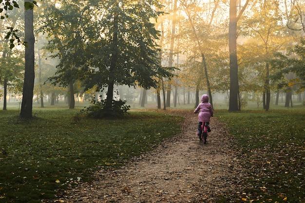 Menina andando de bicicleta em um lindo dia nebuloso de outono ao nascer do sol
