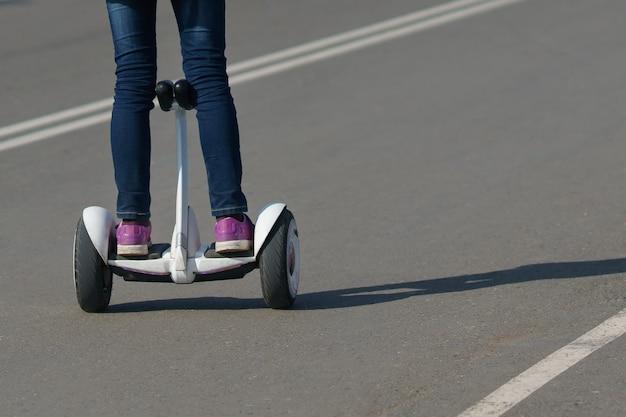 Menina andando de giroscópio em uma estrada para pedestres, copie o espaço