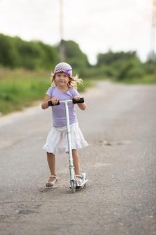 Menina andando de scooter na estrada na zona rural, segurança infantil, infância