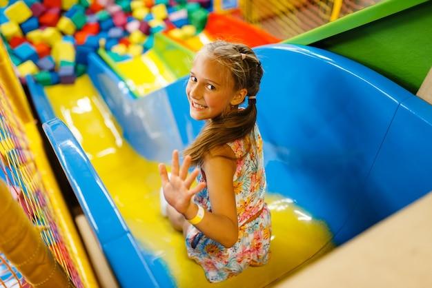 Menina andando em escorregador infantil de plástico, sala de jogos