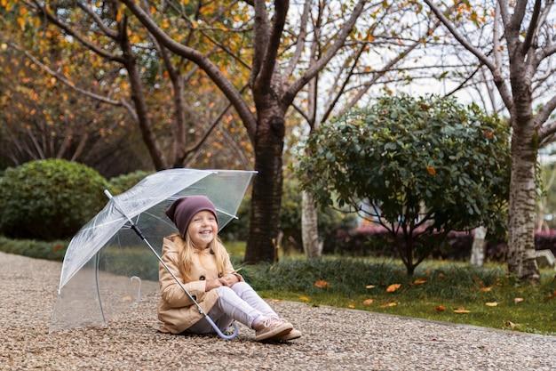 Menina andando em um parque sob um guarda-chuva durante uma chuva