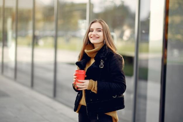 Menina andando em uma cidade de primavera e segurar o café na mão