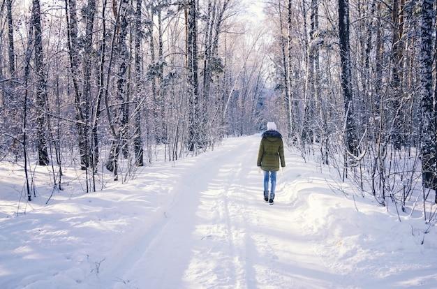 Menina andando na floresta de inverno