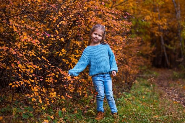 Menina andando na floresta de outono com roupas azuis