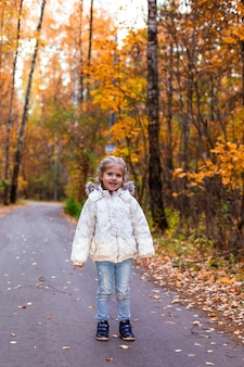Menina andando na floresta de outono com roupas brancas na estrada