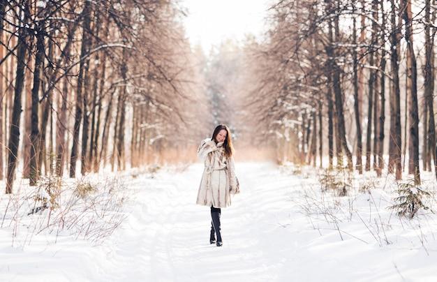 Menina andando na neve. conceito de inverno, frio e pessoas