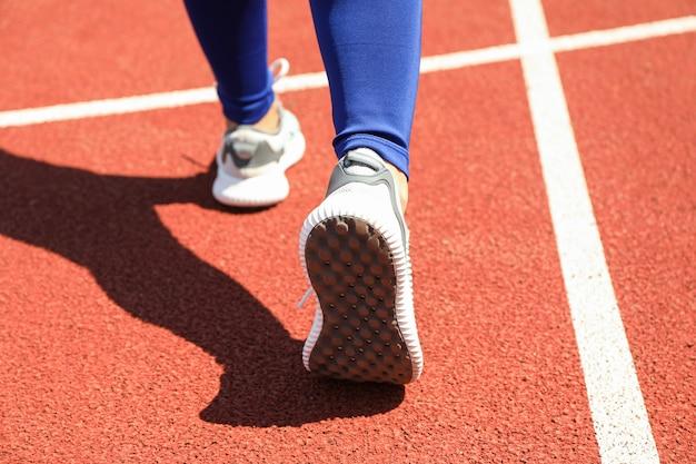 Menina andando na pista atlética vermelha, close-up