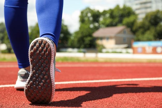 Menina andando na pista atlética vermelha, espaço para texto