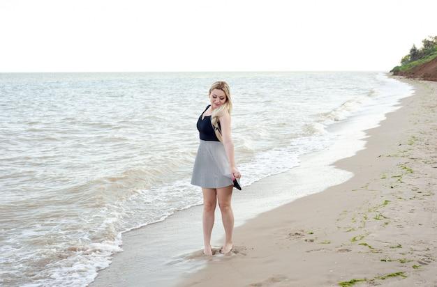 Menina andando na praia em tempo nublado, em um vestido