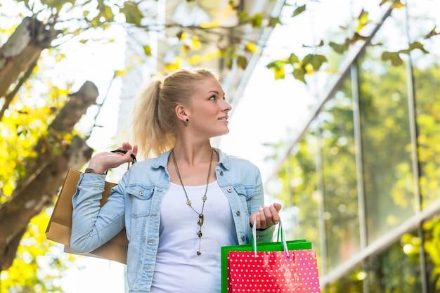 Menina andando na rua com sacolas de compras