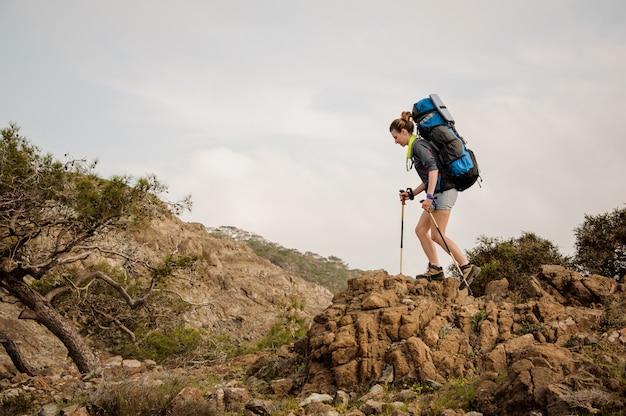 Menina andando nas rochas com mochila para caminhadas