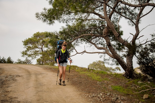 Menina andando no caminho com mochila para caminhadas