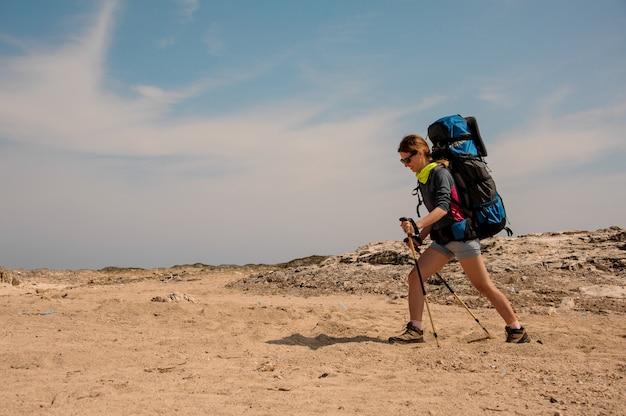 Menina andando no deserto com mochila para caminhadas