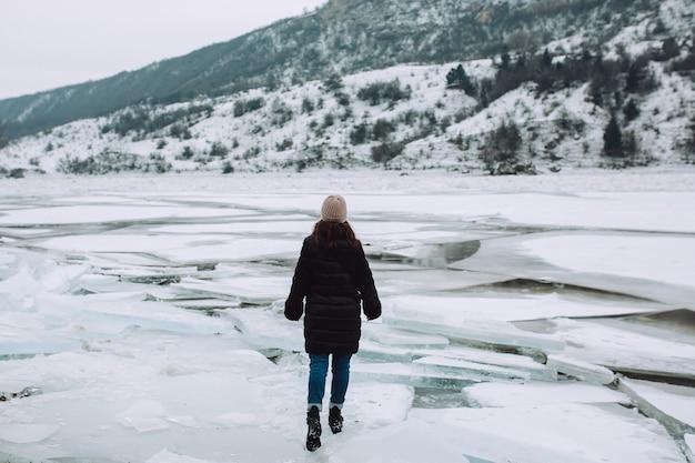 Menina andando no gelo rachado de um rio congelado. dia de inverno.