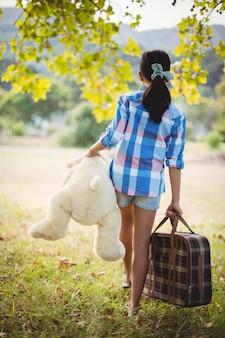Menina andando no parque com uma mala e ursinho de pelúcia