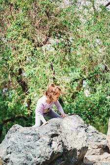 Menina andando no parque no verão, grandes pedras, escalada, caminhadas