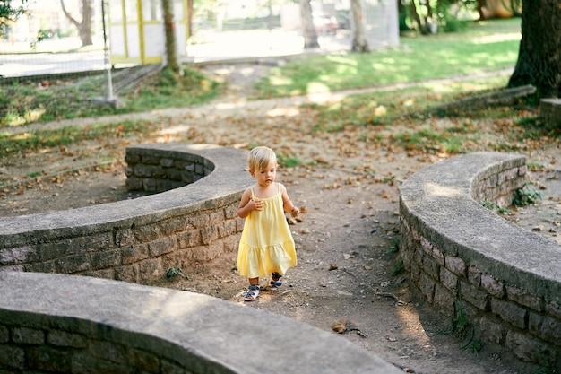 Menina andando no parque perto de paredes de pedra de contenção semicirculares