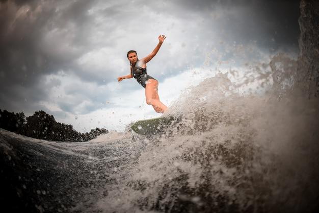 Menina andando no wakeboard no rio no fundo das árvores, levantando as mãos