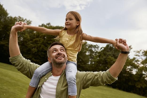 Menina animada brincando com o pai no parque, sentado em seus ombros e sorrindo, eles estão