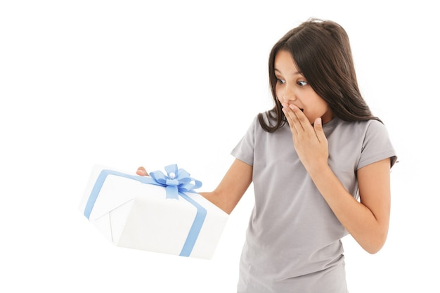 Menina animada chocada segurando uma caixa de presente surpresa.