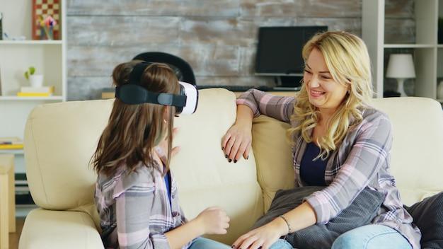 Menina animada com seu fone de ouvido de realidade virtual de sua mãe. infância feliz.